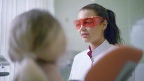 Οδοντίατρος στο οδοντικό γραφείο που μιλά με υπομονετικό και που προετοιμάζεται για τη θεραπεία απόθεμα βίντεο