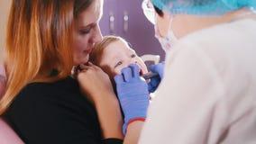 οδοντιατρική  Μια μητέρα που κρατά ένα μωρό απόθεμα βίντεο