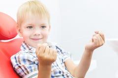 Οδοντική κλινική Υποδοχή, εξέταση του ασθενή Προσοχή δοντιών Ένα μικρό αγόρι με το οδοντικό νήμα κάθεται σε μια οδοντική καρέκλα στοκ φωτογραφίες