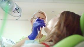 Οδοντικός έλεγχος υγιεινολόγων επάνω στα υπομονετικά δόντια Επαγγελματική εργασία στοματολογίας απόθεμα βίντεο