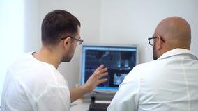 Οδοντικός βοηθός που συζητά με τον οδοντίατρο για το πρόβλημα δοντιών ` s στον των ακτίνων X πυροβολισμό φιλμ μικρού μήκους