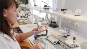 Οδοντικός τεχνικός πορτρέτου με ένα τεχνητό σαγόνι στα χέρια του εργασιακού χώρου με τα εργαλεία και τον εξοπλισμό στο εργαστήριο απόθεμα βίντεο
