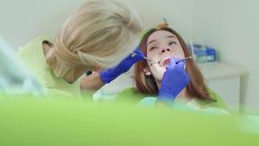 Οδοντικός τεχνικός που εξετάζει τα υπομονετικά δόντια με τα οδοντικά όργανα φιλμ μικρού μήκους