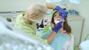 Οδοντικός υγιεινολόγος που εξετάζει τα υπομονετικά δόντια με το στοματικό καθρέφτη και τον οδοντικό έλεγχο απόθεμα βίντεο