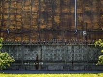 Οδοντωτός - καλώδιο σε έναν γκρίζο συγκεκριμένο φράκτη κατά μήκος των κτηρίων σκουριάς σιδήρου Στοκ Φωτογραφία