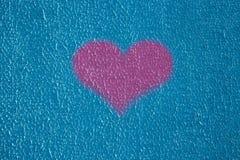 Οδοντωτό μη ίσο μπλε putty ασβεστοκονιάματος τοίχων σύστασης υποβάθρου έξω από το ροζ αγάπης καρδιών στοκ φωτογραφία με δικαίωμα ελεύθερης χρήσης