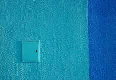 Οδοντωτό μη ομαλό μπλε putty ασβεστοκονιάματος τοίχων σύστασης υποβάθρου έξω από τη σκούρο μπλε ηλεκτρική ενέργεια ασπίδων λουρίδ Στοκ φωτογραφία με δικαίωμα ελεύθερης χρήσης