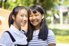 Οδοντωτό πρόσωπο χαμόγελου της ασιατικής στάσης εφήβων δύο υπαίθριας στοκ εικόνες