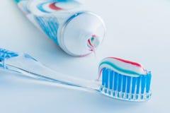 Οδοντόβουρτσα του σαφούς πλαστικού με τις μπλε σκληρές τρίχες, άσπρες μπλε κόκκινες συμπιέσεις οδοντόπαστας από έναν σωλήνα στοκ εικόνες