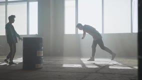 Οδός δύο φίλων που χορεύει μπροστά από το μεγάλο παράθυρο στο εγκαταλειμμένο κτήριο Έφηβοι που κάνουν την κίνηση χορού απόθεμα βίντεο