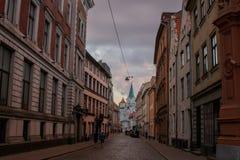 Οδός στην παλαιά πόλη της Ρήγας, που οδηγεί στην άσπρη εκκλησία στοκ εικόνες