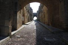 Οδός στην παλαιά πόλη της Ρόδου με το τόξο πετρών στοκ εικόνες