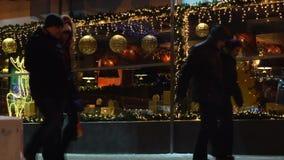 Οδός τη νύχτα στην πόλη με τη διακόσμηση Χριστουγέννων των παραθύρων στο υπόβαθρο του περπατήματος ανθρώπων Ρωσία, Novosibirsk απόθεμα βίντεο