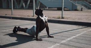 Οδός workout Αθλητικό άτομο αφροαμερικάνων που κάνει το ώθηση-UPS και την άσκηση περιστροφής υπαίθρια Ένας μαύρος παίζει φιλμ μικρού μήκους