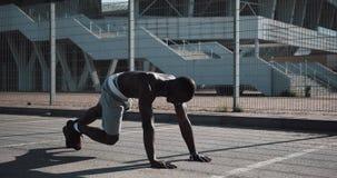 Οδός workout Αθλητικό άτομο αφροαμερικάνων που κάνει το ώθηση-UPS και την άσκηση περιστροφής υπαίθρια Ένας μαύρος παίζει απόθεμα βίντεο