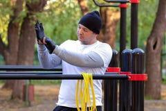 Οδός workout ενός νεαρού άνδρα το ηλιόλουστο πρωί Το άτομο προετοιμάζεται να εκτελέσει ένα φορτίο δύναμης στον προσομοιωτή και φο στοκ εικόνες με δικαίωμα ελεύθερης χρήσης