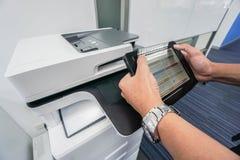 Οθόνη αφής λαβής επιχειρηματιών για το έγγραφο εκτύπωσης από το γραφείο από τον εκτυπωτή γραφείων Στοκ Φωτογραφίες