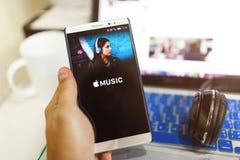 Οθόνη εκμετάλλευσης χεριών ατόμων που πυροβολείται της μουσικής app της Apple που παρουσιάζει στο ανδρο Στοκ Φωτογραφία
