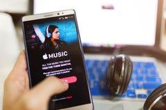 Οθόνη εκμετάλλευσης χεριών ατόμων που πυροβολείται της μουσικής app της Apple που παρουσιάζει στο ανδρο Στοκ Φωτογραφίες