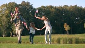 Οικογένεια από τα ΑΜΕΡΙΚΑΝΙΚΑ κυματίζοντας υπόβαθρα στο πάρκο, μπροστινή άποψη φιλμ μικρού μήκους