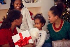 Οικογένεια αφροαμερικάνων που ανταλλάσσει τα δώρα Χριστουγέννων Στοκ Φωτογραφίες