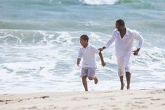 Οικογένεια γιων πατέρων αφροαμερικάνων στην παραλία στοκ φωτογραφία
