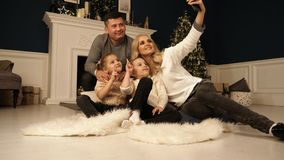 Οικογένεια, διακοπές, τεχνολογία και άνθρωποι - χαμογελώντας μητέρα, πατέρας και μικρά κορίτσια που κάνουν selfie με τη κάμερα στοκ φωτογραφία