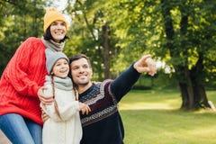 Οικογένεια, εποχή, έννοια σχέσης Η φιλική στοργική οικογένεια έχει τον περίπατο στο πάρκο φθινοπώρου, θαυμάζει την όμορφη φύση, θ στοκ εικόνες