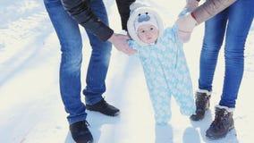 οικογένεια ευτυχής Η μητέρα και ο πατέρας διδάσκουν ένα παιδί για να περπατήσουν στο χειμερινό πάρκο φιλμ μικρού μήκους