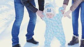 οικογένεια ευτυχής Η μητέρα και ο πατέρας διδάσκουν ένα παιδί για να περπατήσουν στο χειμερινό πάρκο απόθεμα βίντεο