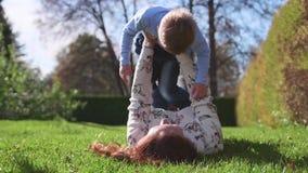 οικογένεια ευτυχής Η μητέρα κρατά το γιο της στα όπλα της, τα χαμόγελα παιδιών Στο υπόβαθρο του ευτυχούς παιδιού ` s ήλιων και ου απόθεμα βίντεο
