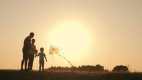 οικογένεια ευτυχής Η οικογένεια το καλοκαίρι στο ηλιοβασίλεμα προωθεί έναν ικτίνο στον ουρανό απόθεμα βίντεο