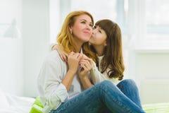 οικογένεια ευτυχής κόρη που αγκαλιάζει και που φιλά την μητέρα εσωτερική Στοκ Εικόνες