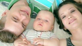 οικογένεια ευτυχής Μπαμπάς Mom και εξάμηνο παλαιό μωρό Οικογένεια που βρίσκεται στο κρεβάτι και που εξετάζει τη κάμερα, χαμόγελο απόθεμα βίντεο