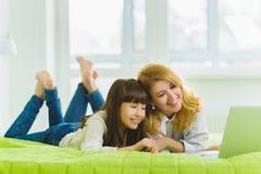 οικογένεια ευτυχής Συνεδρίαση μητέρων και κορών στο κρεβάτι με ένα lap-top Στοκ φωτογραφία με δικαίωμα ελεύθερης χρήσης