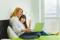 οικογένεια ευτυχής Συνεδρίαση μητέρων και κορών στο κρεβάτι με ένα lap-top Στοκ εικόνα με δικαίωμα ελεύθερης χρήσης
