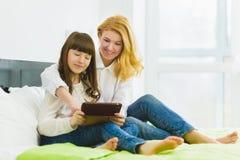 οικογένεια ευτυχής Συνεδρίαση μητέρων και κορών στο κρεβάτι με μια ταμπλέτα Στοκ Εικόνες