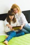 οικογένεια ευτυχής Συνεδρίαση μητέρων και κορών στο κρεβάτι με μια ταμπλέτα Στοκ φωτογραφία με δικαίωμα ελεύθερης χρήσης