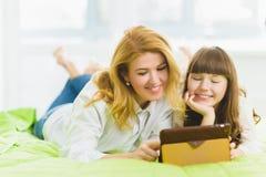 οικογένεια ευτυχής Συνεδρίαση μητέρων και κορών στο κρεβάτι με μια ταμπλέτα Στοκ Φωτογραφίες