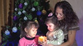 Οικογένεια κάτω από ένα χριστουγεννιάτικο δέντρο με ένα κερί Mom και κόρες στο χριστουγεννιάτικο δέντρο με ένα κερί Ένα μικρό παι απόθεμα βίντεο