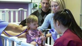 Οικογένεια και κόρη με το προσωπικό στον παιδιατρικό θάλαμο του νοσοκομείου απόθεμα βίντεο