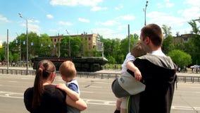Οικογένεια και παιδιά που κυματίζουν το στρατιωτικό εξοπλισμό της Μόσχας στη στρατιωτική παρέλαση απόθεμα βίντεο