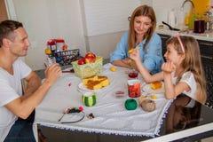 Οικογένεια, κατανάλωση και έννοια ανθρώπων - ευτυχείς μητέρα, πατέρας και κόρη που έχουν το πρόγευμα στο σπίτι στοκ φωτογραφία με δικαίωμα ελεύθερης χρήσης