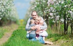 Οικογένεια μεταξύ των ανθίζοντας Apple-δέντρων Στοκ Εικόνες