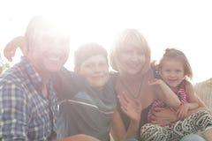 Οικογένεια με δύο παιδιά που κάθονται μαζί και που εξετάζουν τη κάμερα Στοκ Εικόνες