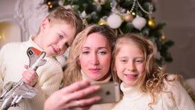 Οικογένεια με δύο παιδιά που κάνουν νέα Χριστούγεννα έτους selfie φιλμ μικρού μήκους