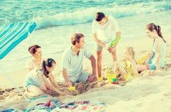 Οικογένεια με τέσσερα παιδιά που παίζουν μαζί στην παραλία θάλασσας Στοκ Εικόνες