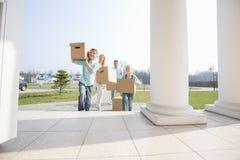 Οικογένεια με τα κουτιά από χαρτόνι που εισάγονται στο καινούργιο σπίτι Στοκ εικόνα με δικαίωμα ελεύθερης χρήσης