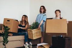 Οικογένεια με τα κουτιά από χαρτόνι στο καινούργιο σπίτι στην κίνηση της ημέρας στοκ φωτογραφία