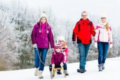 Οικογένεια με τα παιδιά που έχουν το χειμερινό περίπατο στο χιόνι στοκ εικόνες